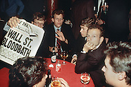 Manhattan, New York City, NY. October 19th, 1987.<br /> Stock Brokers gather in Harry's Bar, a Wall Street institution, showing a newspaper with the headline &quot;Wall St. Bloodbath&quot; in the aftermath of Black Monday, when stock markets around the world crashed.
