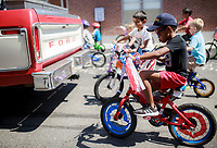 NWA Democrat-Gazette/CHARLIE KAIJO (Right) <br />Lemepe Motlana, 7, of Bentonville rides his bike following the Sam Walton truck during a bike ride at the farmer's market, Saturday, July 7, 2018 at the Square in Bentonville. <br /><br />Area Farmers Markets are participating in a farmers market trail where patrons have passports that are stamped when they visit pariticipating markets. The event takes place through July and is an attempt to celebrate the diversity within the region&Otilde;s markets.