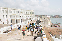 Ghana - Cape Coast - Local pupils visiting the castle. Originally built in 1653, this UNESCO World Heritage Site Castle served as one of the most important slave trading posts along the West Africa coast. Today, it is one of the main attractions in Ghana, with around 90,000 tourists vising it every year. According to environmental experts, much of the West African coast could be submerged by 2099 as a direct consequence of rising sea levels and climate change.