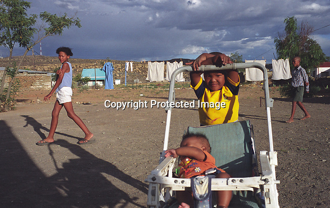 dipprur00030. People Rural Living. Sutherland. Young boy pushing a baby around in a pram. Young girl and boy walking pass in the backround. Washing hanging on the lines.  .©Per-Anders Pettersson/iAfrika Photos.
