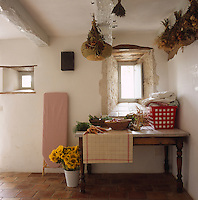 A corner of a rustic kitchen where freshly picked vegetables mingle with a laundry basket full of ironing