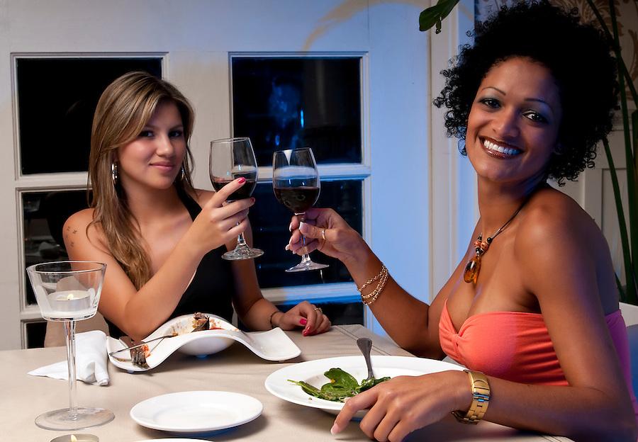 2 Young girls having dinner in a restaurant.