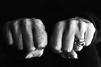 Woman clenching two hands into fists in a fit of aggression.