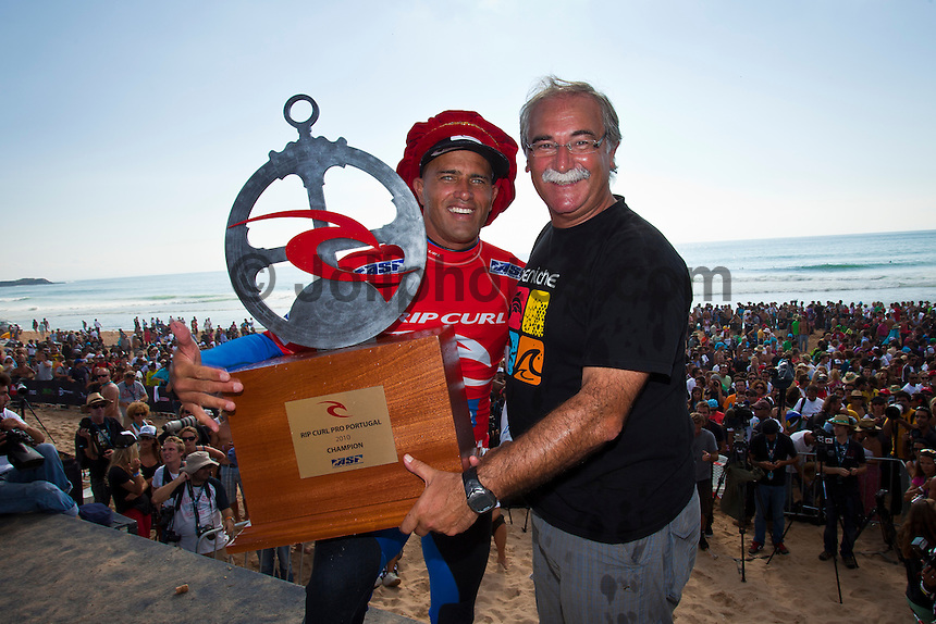 "Kelly Slater (USA) with Antonio Jose Correia (PRT).   SUPERTUBOS, Peniche/Portugal (Thursday, October 14, 2010) -Kelly Slater (USA), 38, former nine-time ASP World Champion and current ASP World No. 1, has collected his 44th elite tour victory, besting current ASP World No. 2, Jordy Smith (ZAF), 22, to take out the Rip Curl Pro Portugal in glassy three-to-five foot (1.5 metre) waves at Supertubos.. .Event No. 8 of 10 on the 2010 ASP World Tour, the Rip Curl Pro Portugal played a vital role in the hunt for the 2010 ASP World Title and was privy to some of the most high-performance surfing the world has ever seen.. .Although composed and relatively under-the-radar throughout the Rip Curl Pro Portugal, Slater struck stealthily in the Final, locking in two solid backhand waves in the shifting conditions, and staving off a late charge from the young South African.. .""It was actually a pretty slow Final with neither of us getting any waves of consequence,"" Slater said. ""I was trying to stay busy but neither of us could get a solid wave. I actually nearly ended up reaching my wave maximum out there so I kind of had to slow down and try to wait for waves that mattered. Jordy (Smith) has all the talent in the world and he's capable of getting a score at any time. It wasn't over until the horn blew."". .En route to an unprecedented 10th ASP World Title, the iconic Floridian moves one step closer to clinching, with a strong possibility of doing so in the upcoming event...Photo: joliphotos.com"