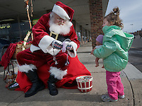 Santa Claus, portrayed by Santa Clarence, a member of the Amalgamated Order of Bearded Santas, offers a piece of chocolate to a youngster who visited with him outside a shipping store where he greeted young and old to hear their Christmas wishes.