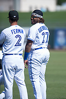 Surprise Saguaros third baseman Vladimir Guerrero Jr. (27) and position coach Andy Fermin (2), both of the Toronto Blue Jays organization, before an Arizona Fall League game against the Salt River Rafters on October 9, 2018 at Surprise Stadium in Surprise, Arizona. The Rafters defeated the Saguaros 10-8. (Zachary Lucy/Four Seam Images)