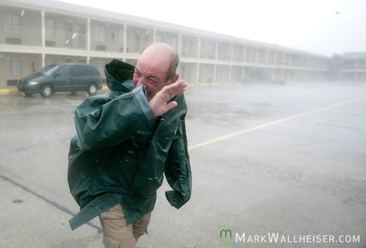Alvin Champagne, a manager at the Days Inn in Morgan City, Louisiana  tries to protect his face from the stinging rain while checking his 140 room hotel for damage as Hurricane Gustav make landfall September 1, 2008.    (Mark Wallheiser/TallahasseeStock.com)