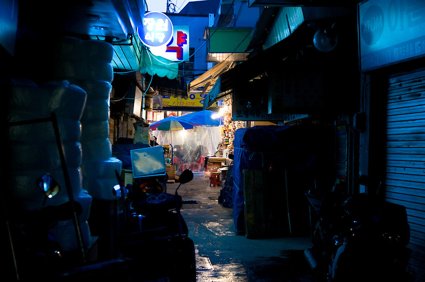 Alley at night in an outdoor market in downtown Seoul, South Korea.