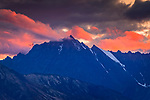 Sunset glow on clouds over rugged peaks of Chugach Mountains, viewed from Glenn Hwy, Southcentral Alaska, Autumn.