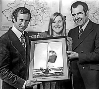 Maeve Bell, Sports Council of N Ireland, presents a painting of Whiskee Too to Bill Whicker, left, and Jim McKee in recognition of their winning a world sailing championship event in New Jersey, USA, in August 1975. 197510140697a<br />