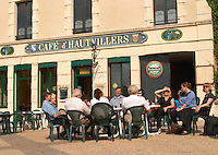 A group of people sitting outside in the sunshine at the Cafe d'Hautvillers, the village of Hautvillers in Vallee de la Marne, Champagne, Marne, Ardennes, France