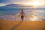 surfer heading out of the water at sunset at Ka'anapali Beach, Maui