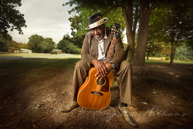 An african-american blues musician sits on a park bench leaning in towards the camera with his guitar.