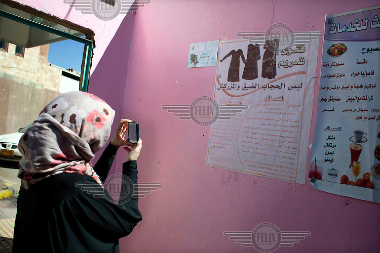 Sarah Jamal Ahmed, a 24 year old sociologist who was one of the activists leading the charge on Change Square in Sana'a photographs a poster dictating women's dress at the women's cafe at The Old University in Sana'a.