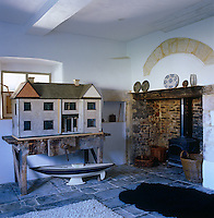 The doll's house in the old kitchen sits on an antique work bench