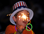 Seven year old Noah of Glastonbury, holds a sparkler over his head, celebrating our 235th year of independence, during the 28th Annual James Dutch Fogarty Independence Day Celebration at Manchester Community College. (Jim Michaud/Journal Inquirer)..