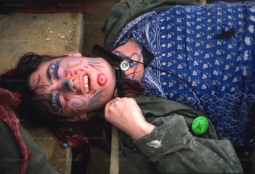 Alexandra Plows chained up with a U-lock. Road Protest actions at Twyford Down, near the Donga pathways, outside Winchester, against the M3 road extension. 1992-94<br /><br />The British Road Protesters movement began in the early 1990s when the Donga tribe squatted Twyford Down to save this beautiful site, a site of scientific interest SSI from the Ministry of transport's road building programme which threatened to destroy the landscape. The Dongas was the name of the ancient walkways, the paths trodden in the middle ages by people walking down to Winchester. A small tribe were joined by people of all walks of life who came to Twyford Down to defend it. A long hard battle over several years ended in the 'cutting' a new motorway built through this ancient monument and destroying it. <br /><br />The Road Protest movement in Britain continued for many years and more battles were fought in London against the MII both at Wanstead then in Leytonstone, and subsequently at Newbury, and in Sussex. the protesters were very inventive in their use of non violent peaceful direct action. They barricaded themselves into squats, made tree houses, tunnels and have huge demonstrations against the bailliffs, police and security who tried to force their way through the defences of this alternative environmental popular movement. Many of the roads were built eventually and many sites of great beauty lost, but the government had to stand down from its road building policy and eventually the programme was halted. the protests cost the government billions. Out of that movement grew many environmental NGOs who have to this day kept fighting for ecological and sustainable environmental solutions rather than following the cult of the car, petrol and roadbuilding..