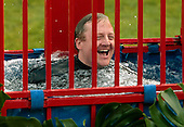 Washington, DC - June 25, 2009 -- White House Press Secretary Robert Gibbs smiles after being knocked into a dunk tank by members of the news media before a luau for members of Congress and their families on the South Lawn of the White House June 25, 2009 in Washington, DC. In a celebration of U.S. President Barak Obama's home state, the South Lawn was decorated with tiki torches and palm huts and the meal prepared by famous Hawaiian chef Alan Wong. .Credit: Chip Somodevilla - Pool via CNP