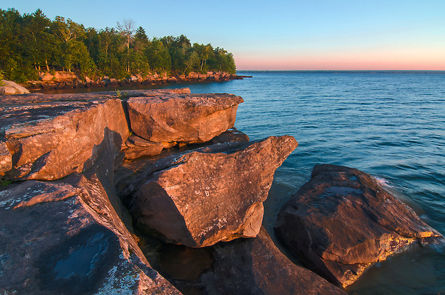 Sunrise Light falls on the rocks and the Lake Superior shoreline of Big Bay Point in Big Bay State Park on Madeline Island in the Apostle Islands in Ashland County, Wisconsin