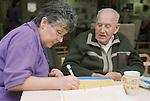 Elderly man talking to female staff nurse while she makes assessment on progress.  MR
