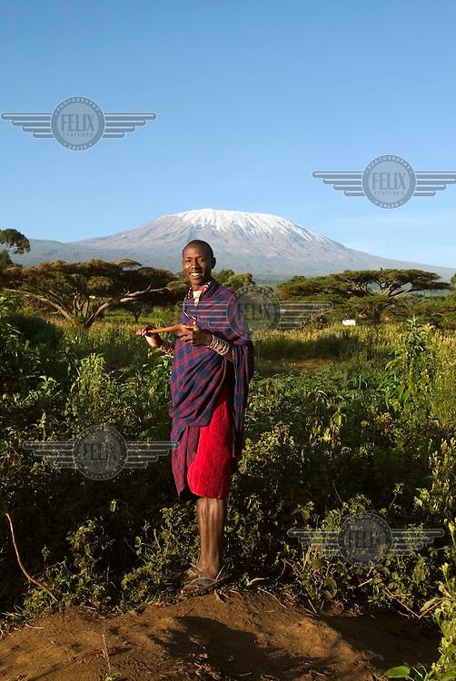 A Masai warrior poses in front of Mount Kilimanjaro mountain.
