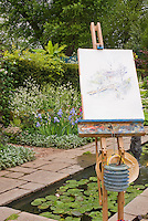 Easel with watercolor drawing in garden setting outdoors with small pond and fountain, painting supplies, stone walkway path, flowers, flowering shrubs, trees, herbs, waterlilies