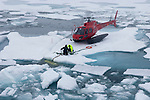 Helicopter and pilots on a small ice floe attaching a cable onto the research submersible trapped in an ice floe, Arctic Ocean.