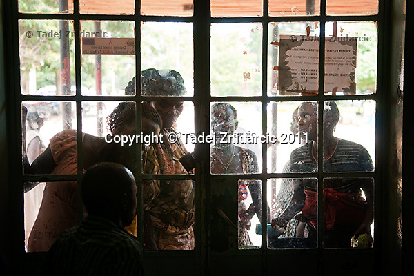 Relatives of expecting mothers plead with the guard to be let into maternity ward of Arua Hospital, Uganda. Due to overcrowding only a limited number of people are allowed into maternity ward.