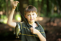 Stock Photo of a Boy Holding up a Fish on a Hook and Line
