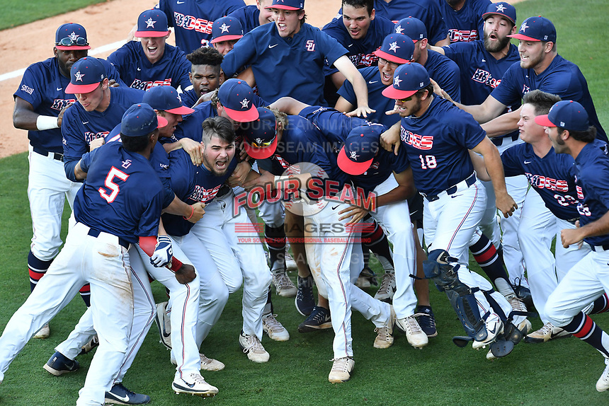 Samford's Ayrton Schafer (13), hatless in the front row, is swamped by teammates after he got the winning hit in the bottom of the ninth inning as No. 6 seed Samford beat No. 1 seed Mercer, 5-4, at the Southern Conference Baseball Championship on Friday, May 26, 2017, at Fluor Field at the West End in Greenville, South Carolina. (Tom Priddy/Four Seam Images)