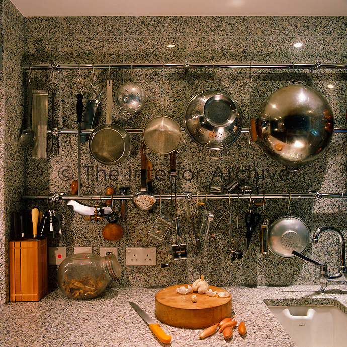 A collection of collanders, sieves and kitchen utensils hangs from a rack in this black and white granite kitchen