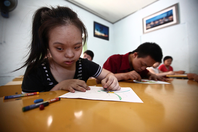 A girl colors a page at a center for children affected by dioxin exposure in Da Nang, Vietnam. The Da Nang Association for Victims of Agent Orange/Dioxin says that 5,000 people - including more than 1,400 children - around the city suffer from mental and physical disabilities because of dioxin exposure, a legacy of the U.S. military's use of Agent Orange and other herbicides during the Vietnam War more than 40 years ago. About 200 children attend three centers operated by the group, giving their parents the opportunity to work away from home, often for the first time. The Vietnam Red Cross estimates that 3 million Vietnamese suffer from illnesses related to dioxin exposure, including at least 150,000 people born with severe birth defects since the end of the war. The U.S. government is paying to clean up dioxin-contaminated soil at the Da Nang airport, which served as a major U.S. base during the conflict. But the U.S. government still denies that dioxin is to blame for widespread health problems in Vietnam and has never provided any money specifically to help the country's Agent Orange victims. May 28, 2012.