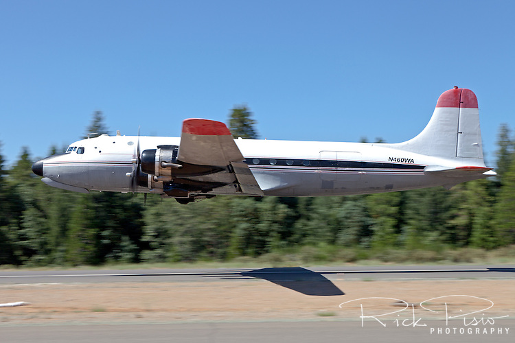 DC-4 460WA, an aircraft owned by Florida Air Transport and currently flying out of the now retired Castle Air Force Base in Atwater, CA, keeps the altitude low during a take off at Nevada County Airport in July of 2013.