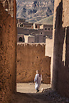 Traditional dressed man walks through an alley in a kasbah.