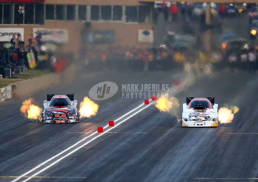 Jul. 18, 2014; Morrison, CO, USA; NHRA funny car driver Cruz Pedregon (right) races alongside Matt Hagan during qualifying for the Mile High Nationals at Bandimere Speedway. Mandatory Credit: Mark J. Rebilas-
