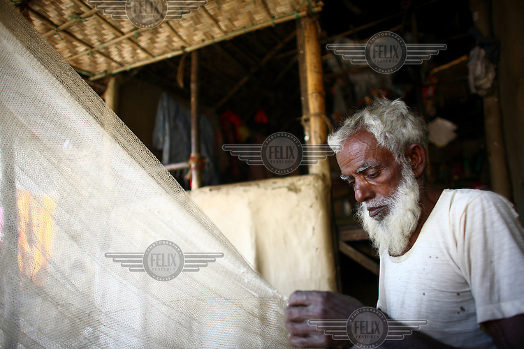 60 year old Alauddin Mia weaves a fishing net outside his home in Sunamganj. He received a microfinance loan from IFAD (International Fund for Agricultural Development).