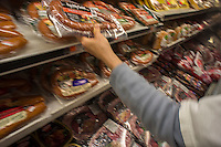 A customer in a supermarket in New York grabs a tasty Smithfield Foods smoked sausage on Thursday, May 30, 2013. The Chinese meat processor Shuanghui has agreed to purchase Smithfield, the world's largest hog producer, for approximately $4.72 billion. Smithfield brands include Armour, Farmland and Smithfield. The purchase, pending approval, would be the largest acquisition by a Chinese company of a U.S. business.  (© Richard B. Levine)
