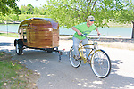A middle-aged man pulling a 2005 Homebuilt Woodstrip teardrop with his bicycle.
