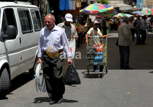 Palestinians shop at a market in the West Bank City of Hebron, June 17, 2014. Thousands of Israeli soldiers have been deployed to surround Hebron, erecting checkpoints and raiding houses following the disappearance of three Israeli teenagers Thursday night, an Israeli official said. Photo by Mamoun Wazwaz