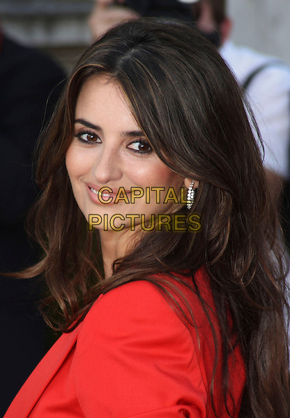 "PENELOPE CRUZ.Attending the UK Film Premiere of ""Broken Embraces"" (Los Abrazos Rotos) at Somerset House, London, England, UK, July 30th 2009..portrait headshot red jacket smiling back over shoulder looking silver hoop earring.CAP/JIL.©Jill Mayhew/Capital Pictures"