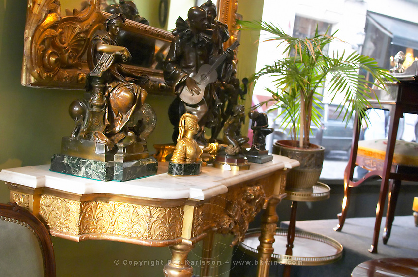 Interior of an antique shop in the San Telmo district around Plaza Dorrego Square, bronze statues of varying sizes on a console table with marble table top and gilt under part and legs. Calle Defensa Defence street Buenos Aires Argentina, South America