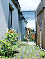 The entrance to the house is via the new extension which is faced with sequoia weatherboard and is connected to the original house by a glassed-in corridor