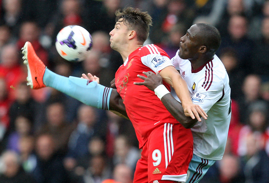Southampton's Jay Rodriguez holds of West Ham United's Guy Demel<br /> <br /> Photo by Kieran Galvin/CameraSport<br /> <br /> Football - Barclays Premiership - Southampton v West Ham United - Sunday 15th September 2013 -  St Mary's Stadium - Southampton<br /> <br /> &copy; CameraSport - 43 Linden Ave. Countesthorpe. Leicester. England. LE8 5PG - Tel: +44 (0) 116 277 4147 - admin@camerasport.com - www.camerasport.com