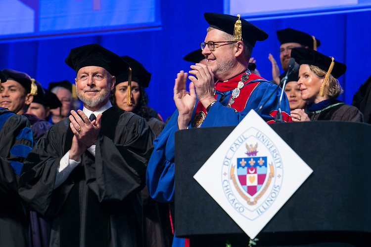Craig W. Hartman, left, world-renowned architect, and the Rev. Dennis H. Holtschneider, C.M., president of DePaul University, greet the graduates Sunday, June 11, 2017, during the DePaul University College of Science and Health and College of Liberal Arts and Social Sciences commencement ceremony at the Allstate Arena in Rosemont, IL. The Rev. Dennis H. Holtschneider, C.M., president of DePaul University looks on. (DePaul University/Jamie Moncrief)