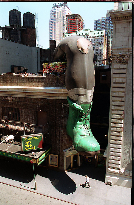 Theater District pedestrian oblivious to the inflation team on roof of the Broadhurst Theatre pumping air into  sculptor Ann Slavit's 75-foot-long Giant's Boot.