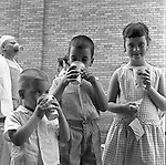 West Mifflin PA: Cathy, Brady and Michael Stewart quenching their thirst before going on the next ride at Kennywood Park - 1956