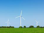 Wind turbine generators in a green field under blue sky. Ontario, Canada.