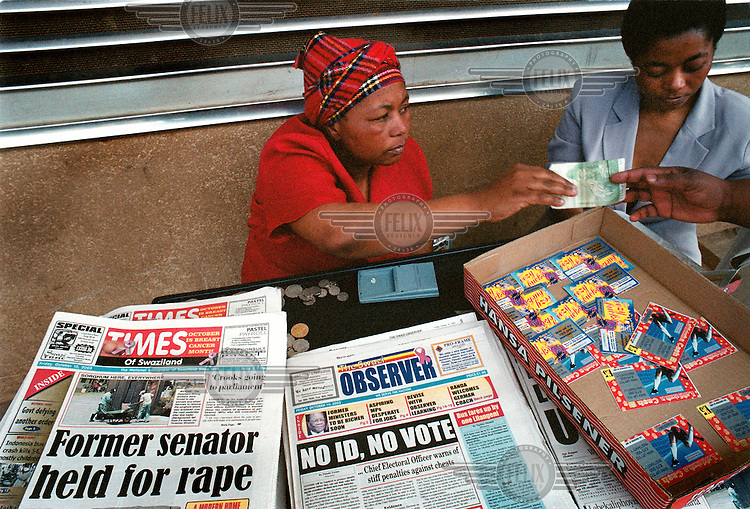 Newspaper vendors on the street selling lottery tickets using South African currency.