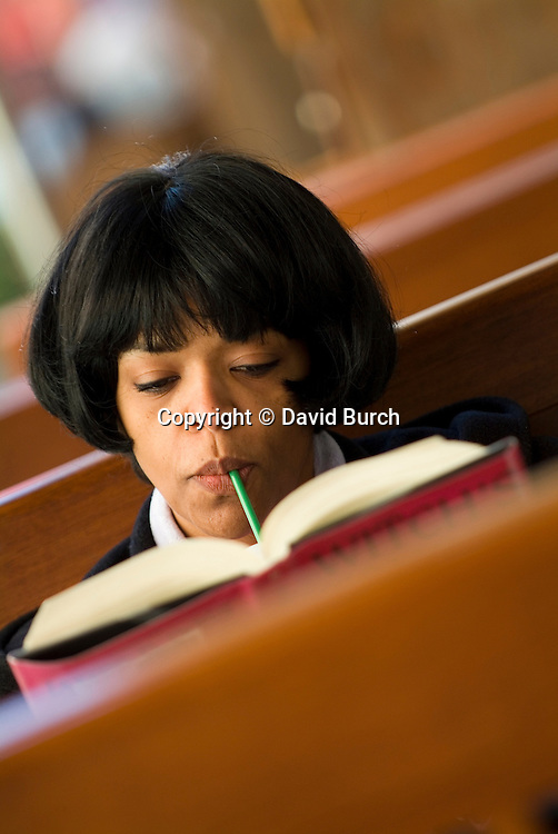 Woman reading book,sipping coffee with straw, close-up