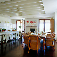 The contemporary kitchen/dining room is furnished with a rustic table and wicker chairs